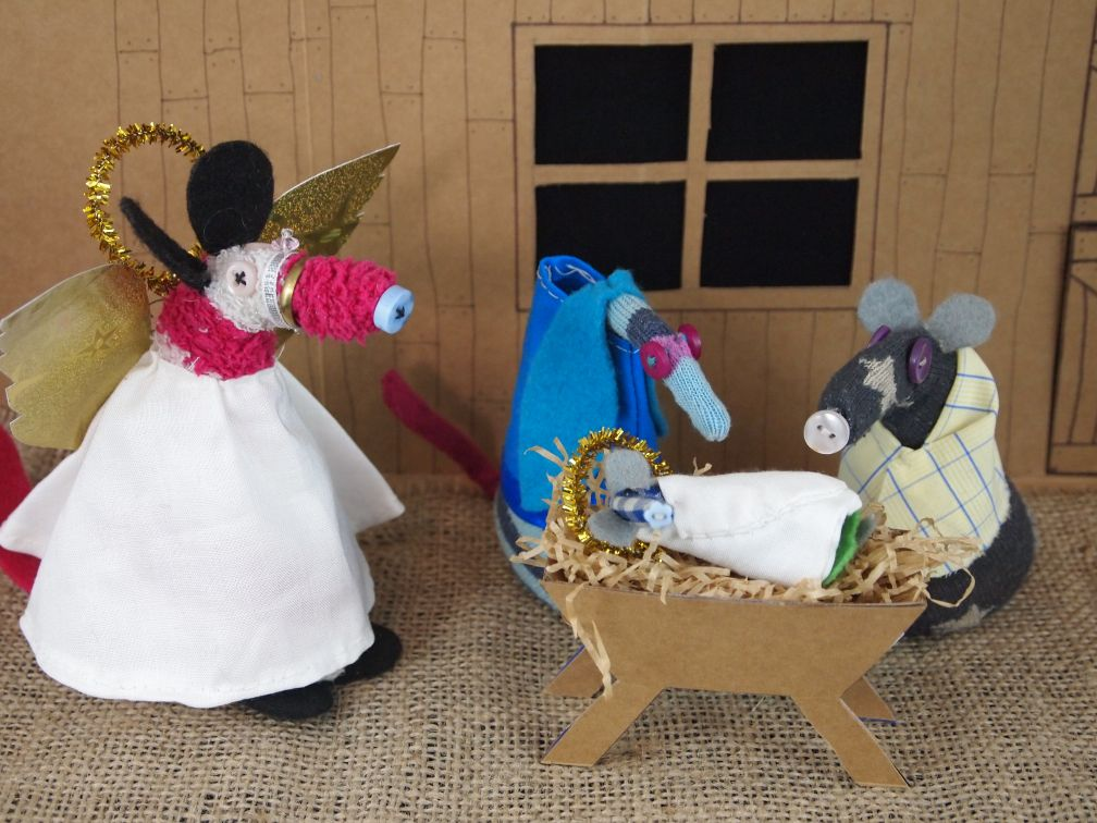 Ofelia and Vincent are dressed as Mary and Joseph, Micro is wrapped in white in the crib and Matilda is an angel in white with gold wings and halo