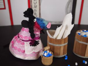 Ratvaark is Widow Twankey in pink frock and black pigtails with a wash tub