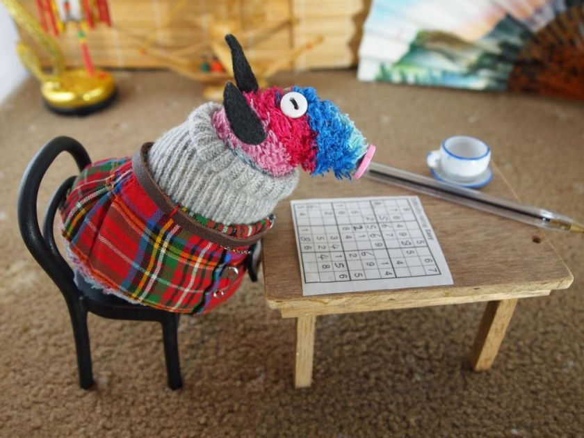 Ratvaark sits at a table with a cup of tea and a sodoku puzzle