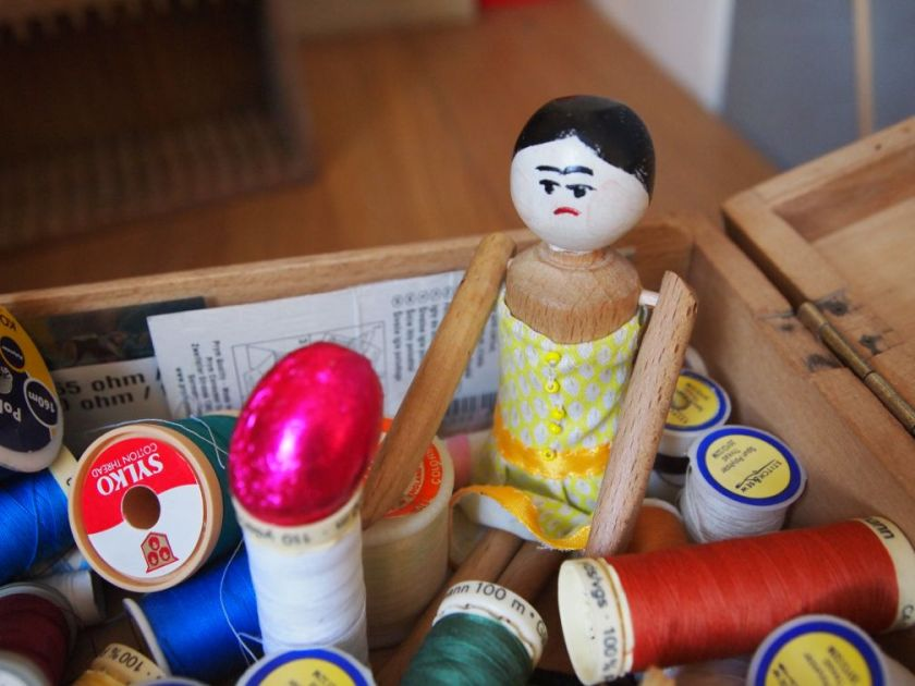 Peggy sits in a tray of sewing threads, with an egg balanced on one of the reels