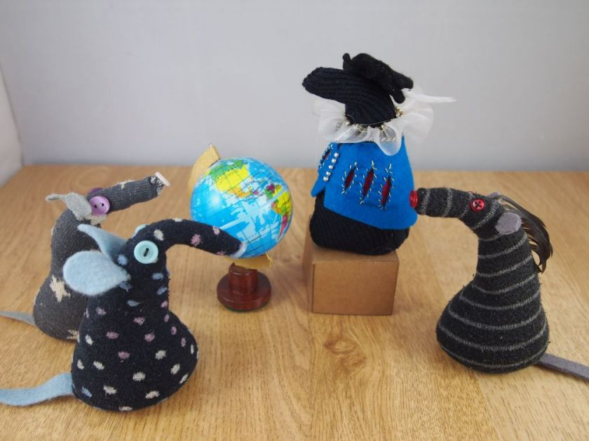 The vaarks look at a mannequin in a doublet and medieval hat, which is looking at a globe