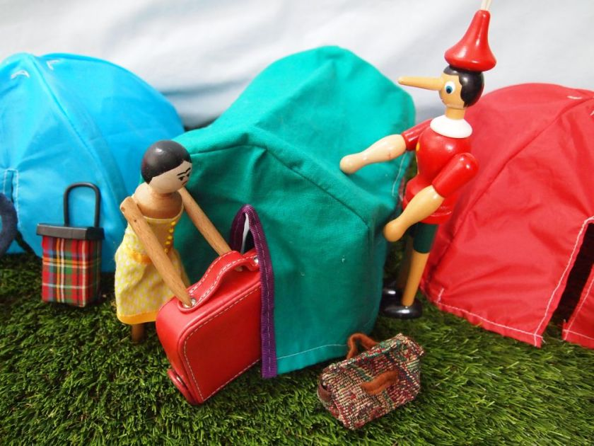 Peggy and Gino put a large suitcase into the scout tent