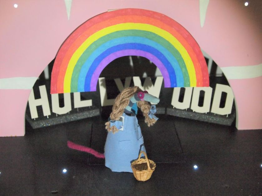 A rainbow appears on the stage behind Dorothy