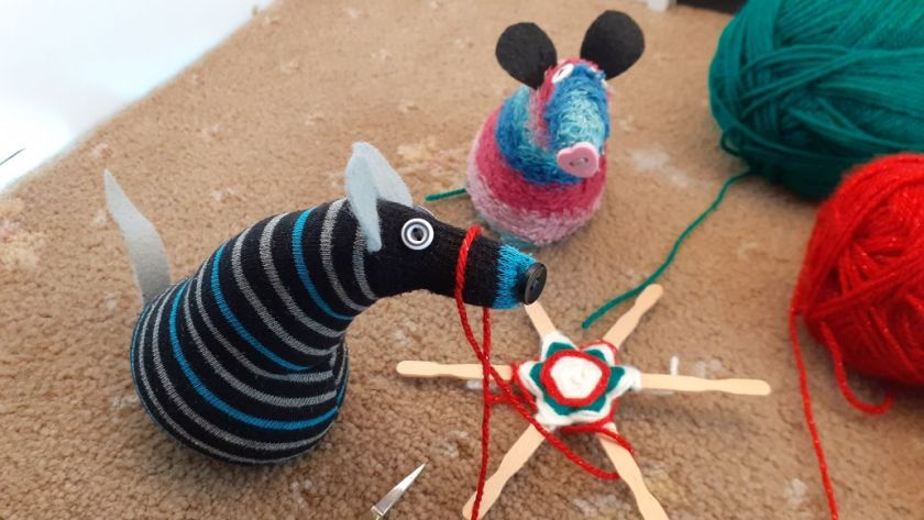 ratvaark watches as Hypno creates different patterns with red white and green yarn