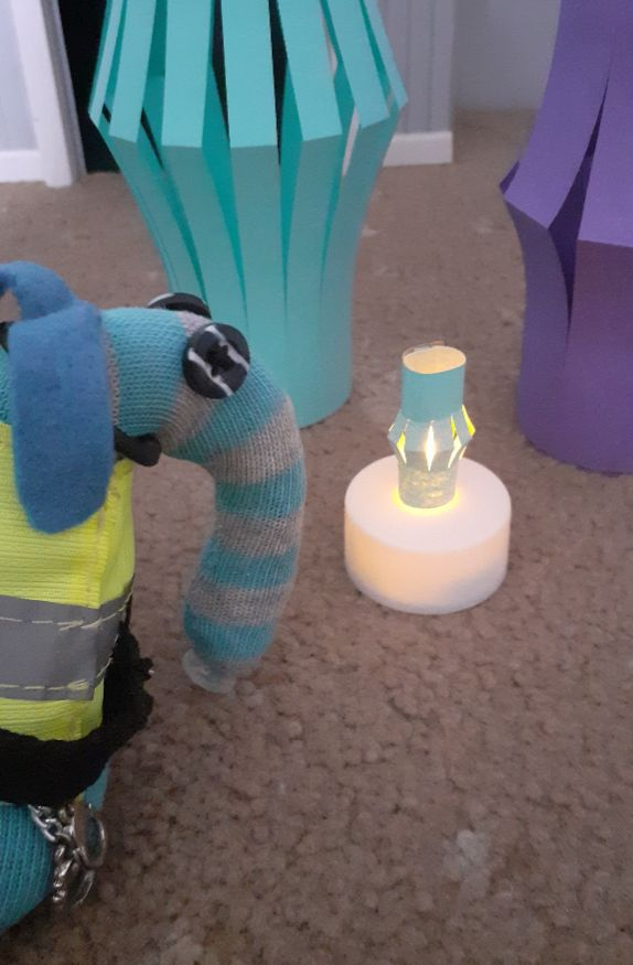 Arnold looks at a tiny lantern that just fits over the fake flame