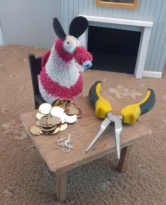 matilda sits at a table with earring hooks, pliers and a pile of shiny gold discs