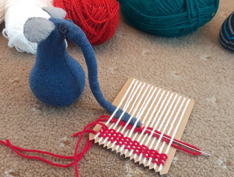 Ernest pushes the needle through and starts to get his snozzle caught in the threads.