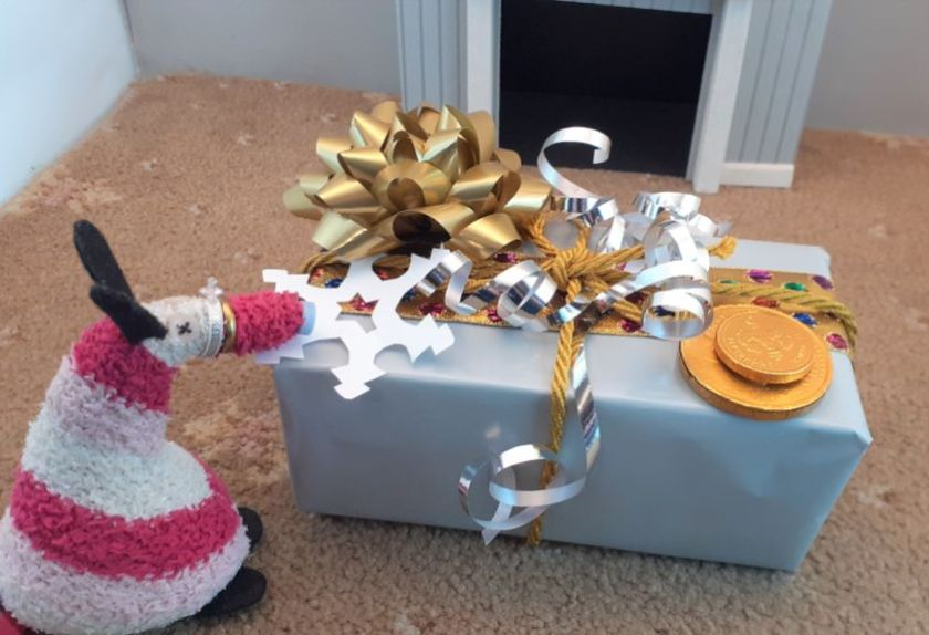 Matilda adds a paper snowflake tucked into the ribbon