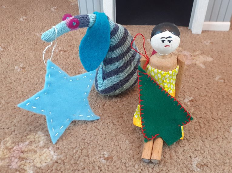Ofelia holds up her star with white stitching, and Peggy has edged her tree shape with red blanket stitch.