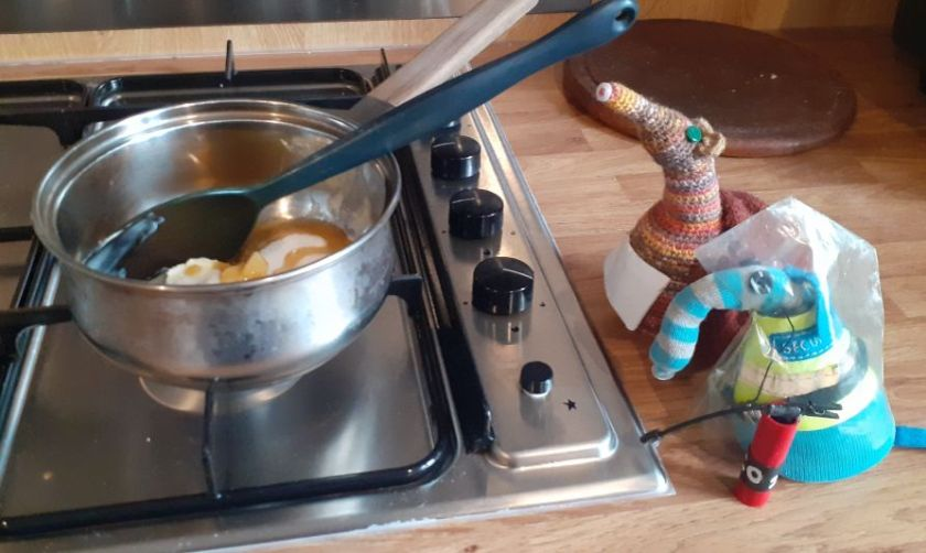 Ernest and Esther watch a pan heating on the stove.