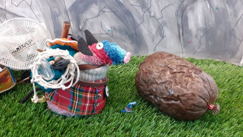 Ratvaark and Nano look at a wrapped haggis