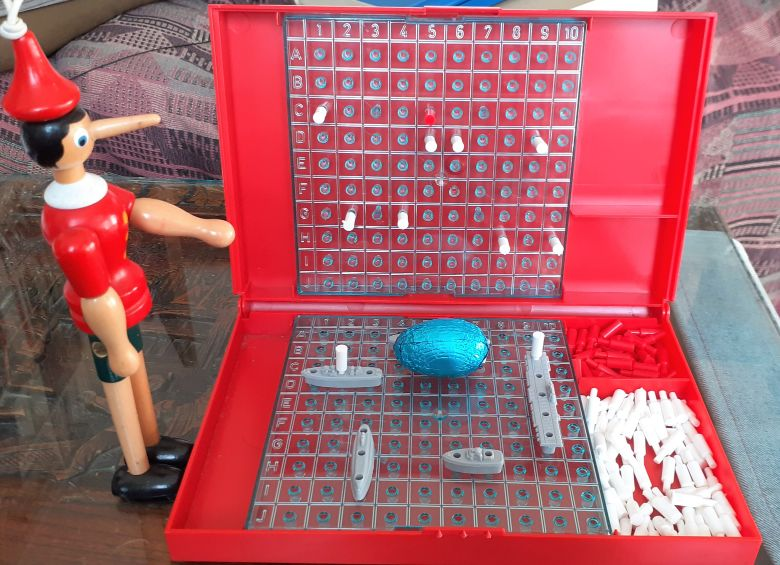 Gino looks at a Battleships board with model ships and pegs in it, and an eggs sitting in the middle