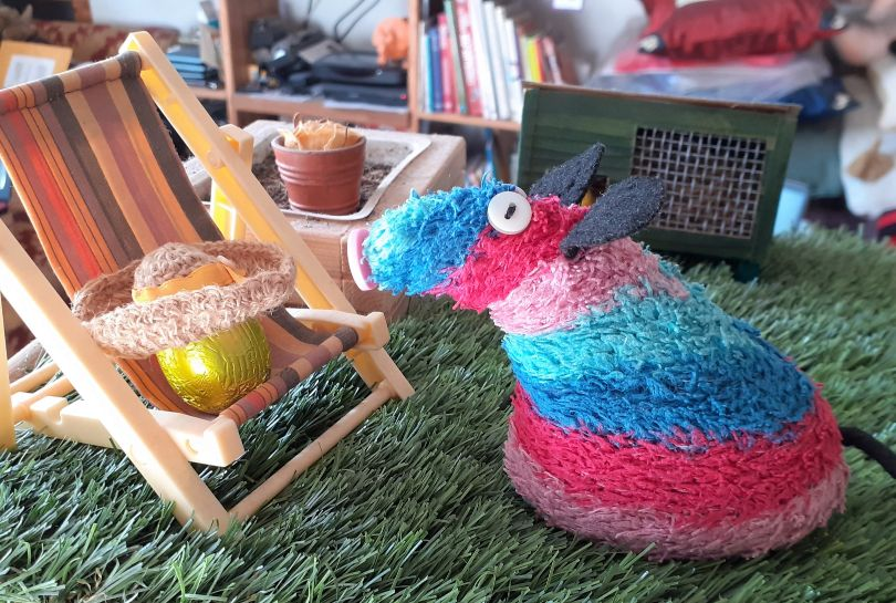 Ratvaark looks at an egg sitting in the little deckchair, with a straw hat on it.