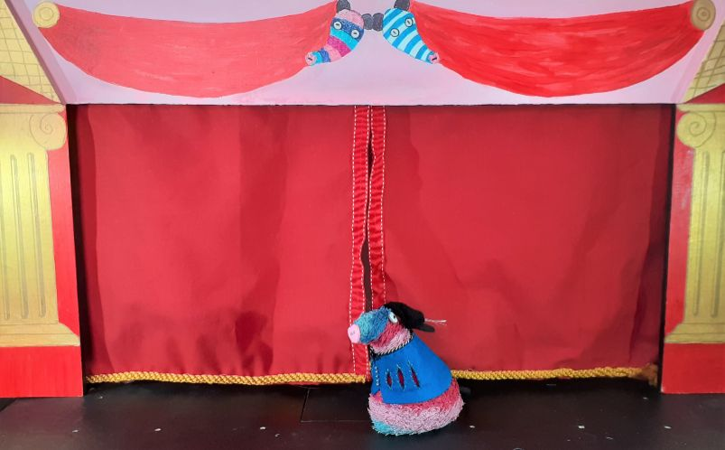 Ratvaark in a tunic and feathered hat, faces the audience on the stage of the Vaark Theatre,