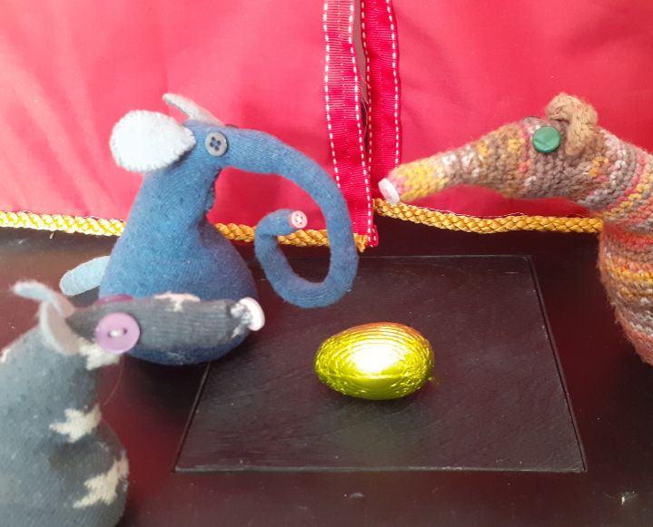 Esther, Vincent and Ernest look at a gold foil wrapped egg.