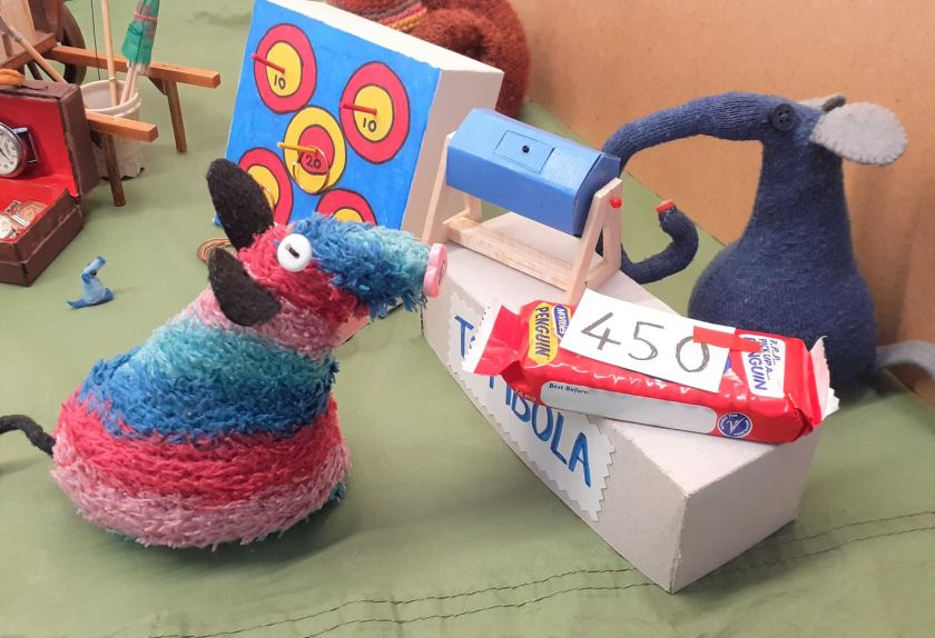 Ratvaark talks to Ernest who has a tombola tumbler and a Penguin biscuit with a numbered ticket on it.
