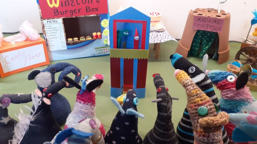 The vaarks are all gathered round a puppet booth with a Mr Punch and a Crocodile puppet showing. Peggy's legs stick out at the bottom of the booth.