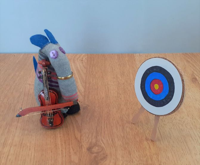 Dim has a violin and bow, standing by an archery target