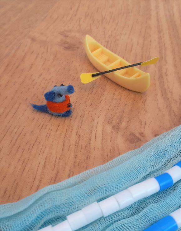 Nano has a tiny canoe and paddle and wears an orange lifejacket