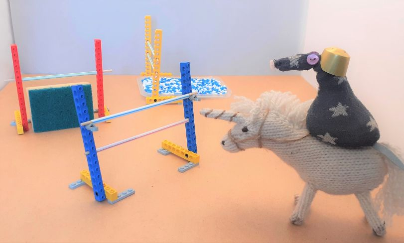 an arena with show jumps set up. Vincent rides a knitted unicorn to the first jump