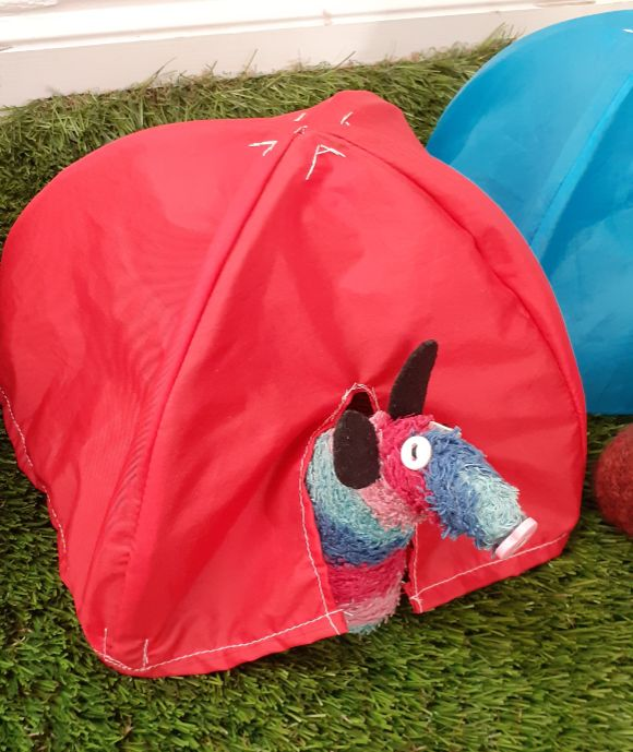 Ratvaark looks out of a red pop-up festival tent