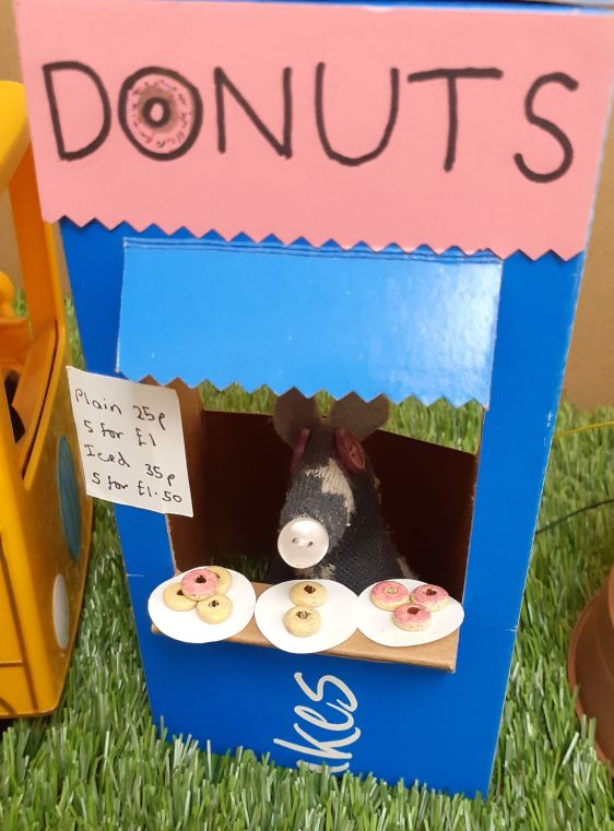 Vincent is in the donut stall with plates of donuts ready to sell
