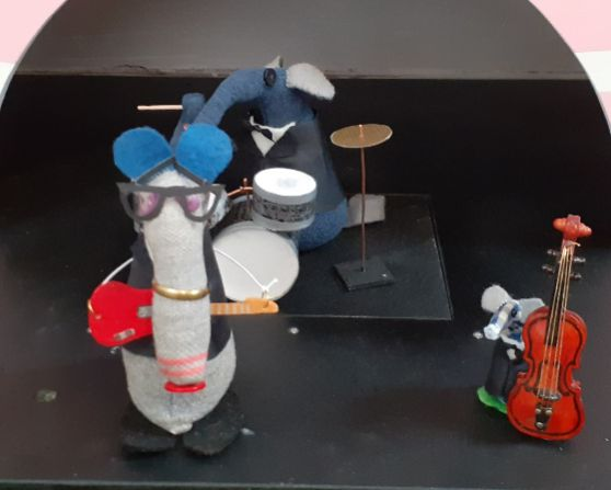 Dim is dressed as Buddy Holly with glasses and guitar, Ernest plays drums and Micro has a double bass. All wear dinner jackets and bow ties.