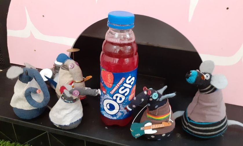Blur and Oasis are on stage together with a bottle of Oasis soft drink.