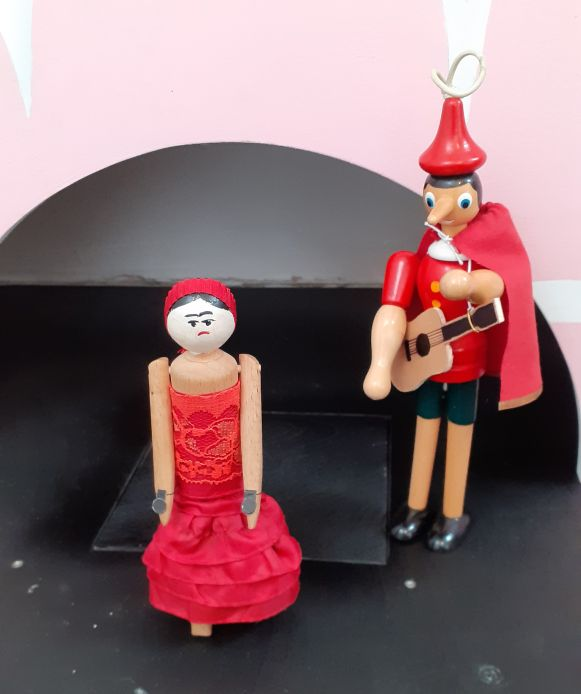 Peggy wears a red flounced dress, and Gino wears a red cape and plays a Spanish guitar.