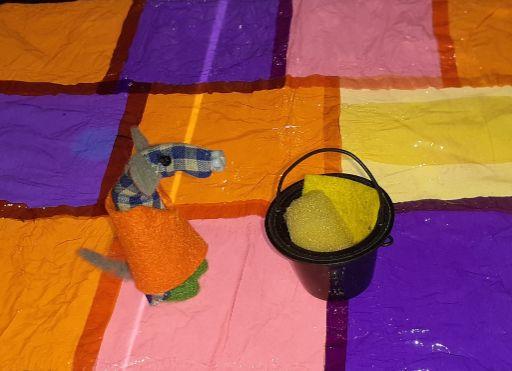 Microvaark is on the dancefloor in an orange overall, with a bucket and sponge