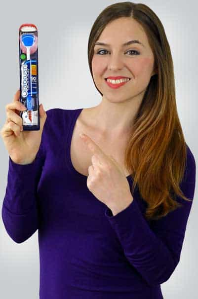 woman holding an Orabrush tongue scraper