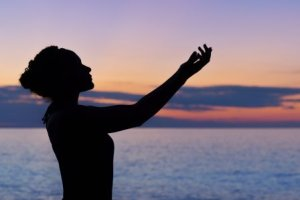 silouette of woman holding hands up against a sunset background