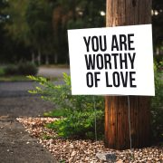 You are worthy of love sign on a tre
