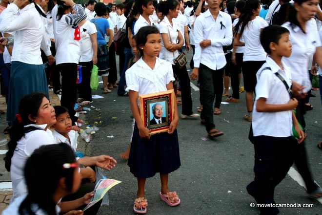 A young Cambodian girl holds a framed photograph of Norodom Sihanouk.
