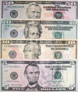 Four different dollar bills placed on a flat surface.