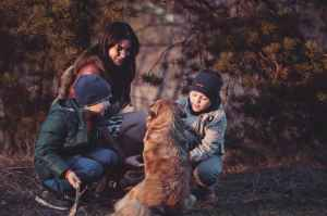 A woman with two boys in nature playing with a dog during fall