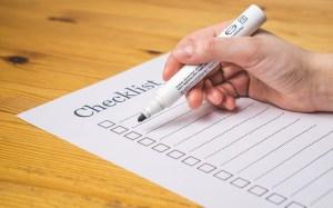 Hand holding a marker over an empty Checklist sheet.