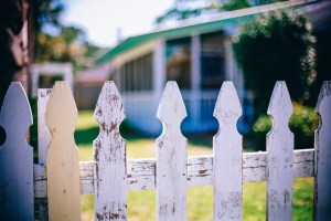 A close up of a white picket fence and a house.