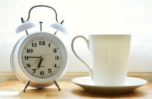 A white alarm clock next to a white coffee mug.
