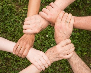 People holding their hands as a sign of a team spirit.