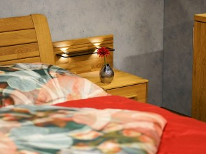 A close up a bed and a nightstand.