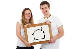 a couple holding a picture of a house