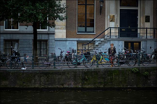 Une femme debout sur un pont derrière une file de vélos garés.