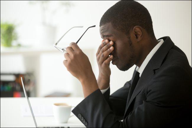 Un homme assis devant son ordinateur portable, tenant ses lunettes et se frottant les yeux.