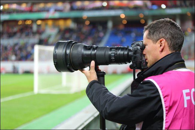 Un photographe avec un grand zoom optique lors d'un match de football.