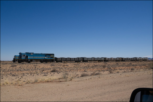 Un train avec le rétroviseur d'une voiture au premier plan.