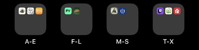 Quatre dossiers sur un écran d'accueil iOS étiquetés par ordre alphabétique.