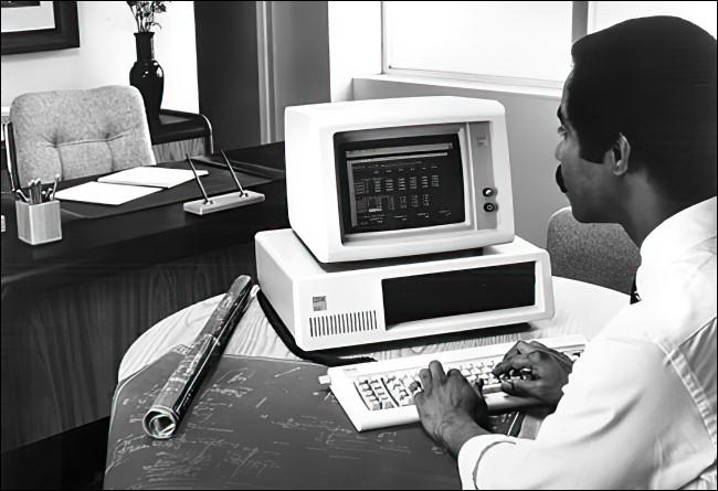 Un hombre que trabaja en una IBM PC 5150.