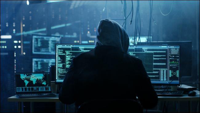 Ein dunkler Hacker in einem Hoodie, der vor einem Computer sitzt.