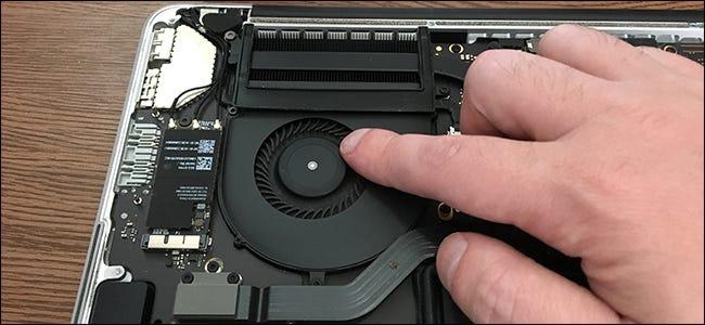 Un doigt touchant le ventilateur de refroidissement à l'intérieur d'un MacBook Pro.